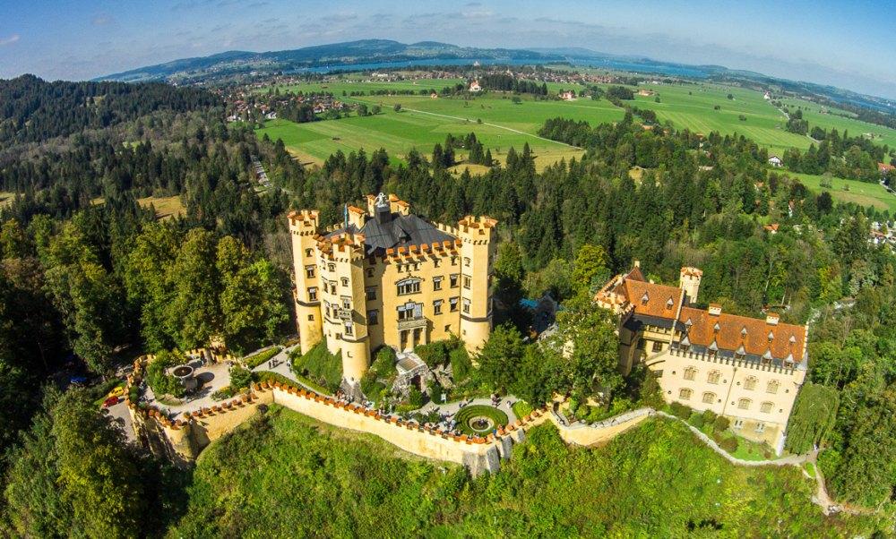 Замок с двух сторон окружен озерами и густым лесом